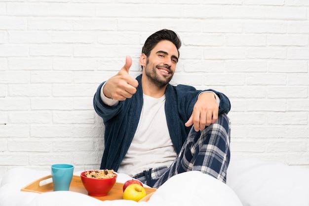 何かが起こったのでドレッシングガウンと親指で朝食をとってベッドの男 Premium写真