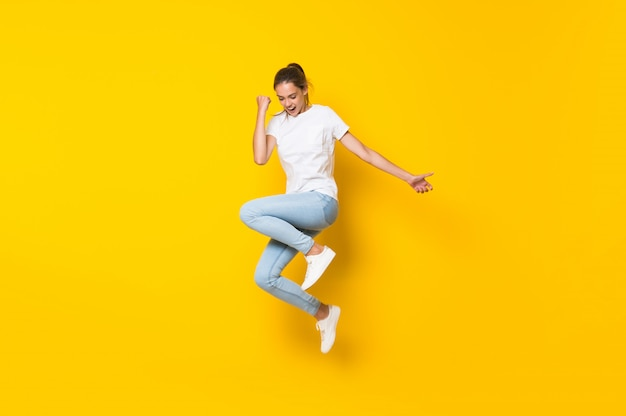 Молодая женщина прыгает через изолированную желтую стену Premium Фотографии