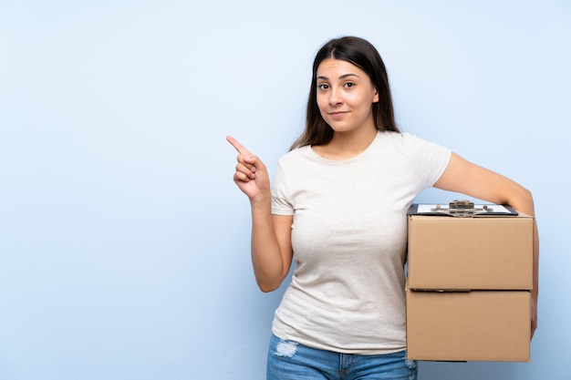 製品を提示する側を指している青いレンガの壁の上の若い配達の女性 Premium写真