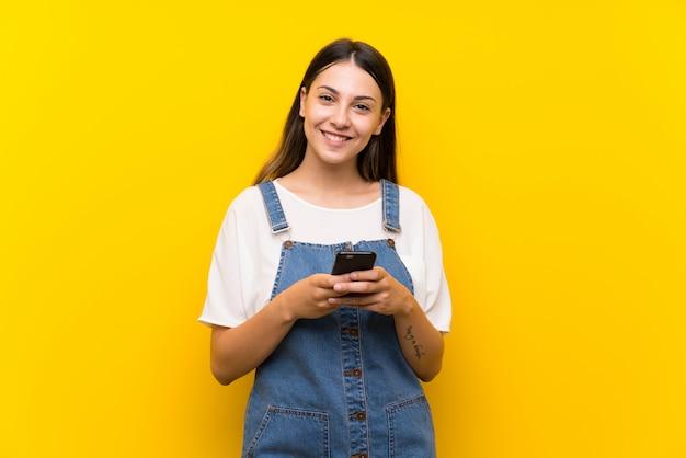 携帯電話でメッセージを送信するダンガリーの若い女性 Premium写真