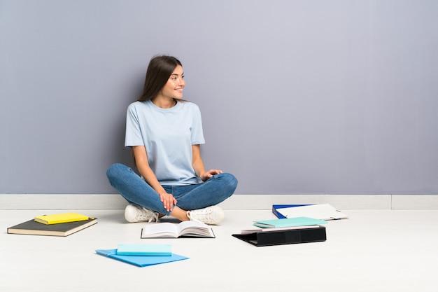 側にいる床に多くの本を持つ若い学生女性 Premium写真
