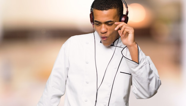 ヘッドフォンで音楽を聴くと踊る若いアフロアメリカンシェフ男 Premium写真
