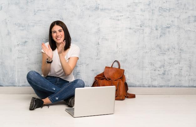 会議でのプレゼンテーション後拍手床に座っている学生女性 Premium写真