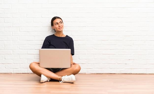 笑いと見上げる床に座ってラップトップを持つ若い女性 Premium写真