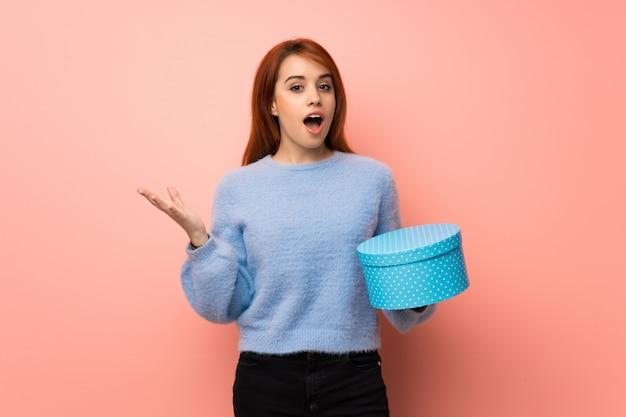 ピンクのギフトボックスを手で保持している若い赤毛の女性 Premium写真