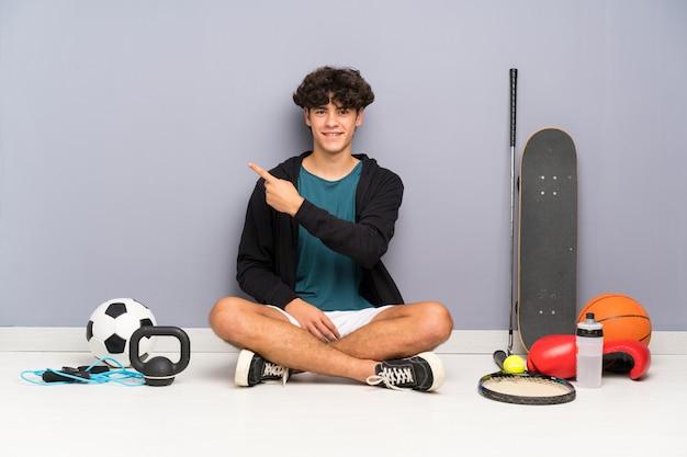 側に指を指している多くのスポーツ要素の周りの床に座って若いスポーツ男 Premium写真