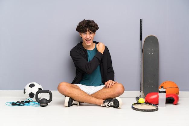 勝利を祝う多くのスポーツ要素の周りの床に座っている若いスポーツ男 Premium写真