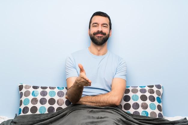 かなりの量を閉じるために手を振ってベッドの男 Premium写真