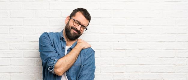 努力をしたための肩の痛みに苦しんでいる白いレンガの壁の上のひげを持つハンサムな男 Premium写真