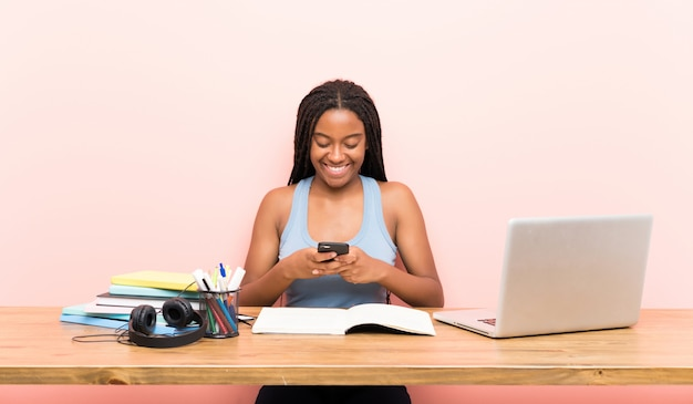 Афро-американский подросток студент девушка с длинными заплетенными волосами на рабочем месте, отправив сообщение с мобильного телефона Premium Фотографии