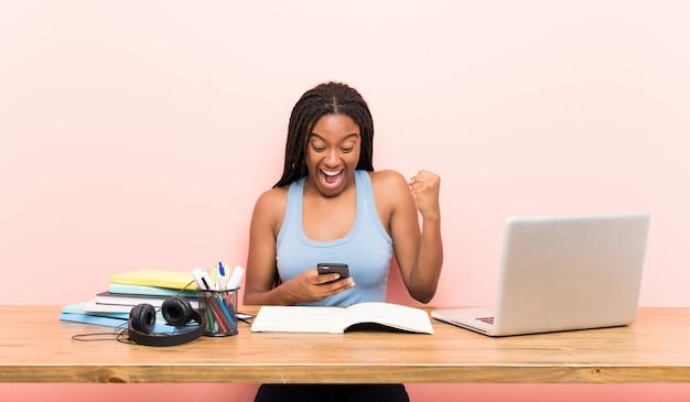 Афро-американский подросток студент девушка с длинными заплетенными волосами на рабочем месте удивлен и отправив сообщение Premium Фотографии