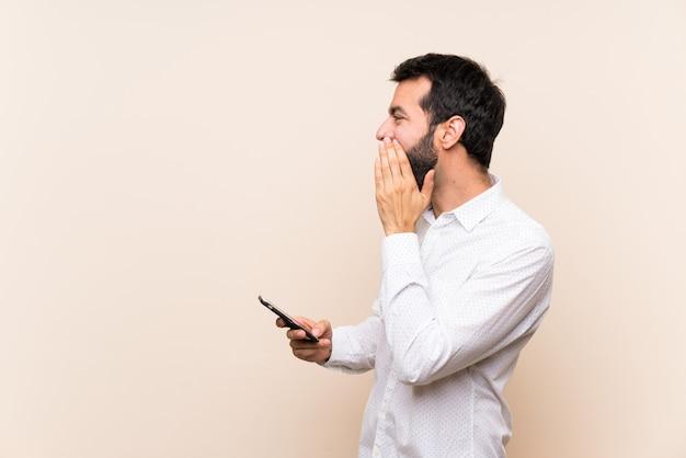 口を大きく開いて外側にモバイル叫びを保持しているひげを持つ若者 Premium写真