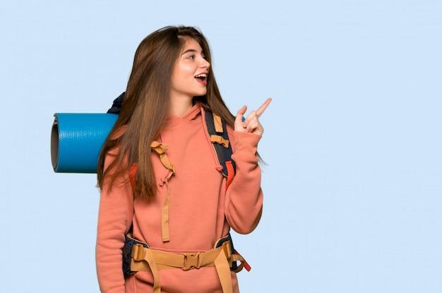 ハイカーの女の子が青の横位置で側に指を指す Premium写真