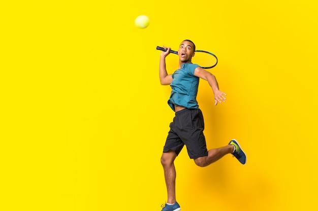 分離された黄色の上のアフロアメリカンテニスプレーヤー男 Premium写真