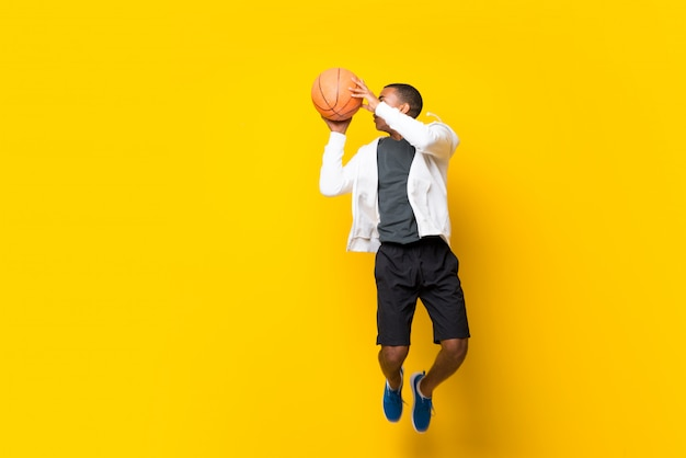 孤立した黄色の上のアフロアメリカンバスケットボールプレーヤー男 Premium写真