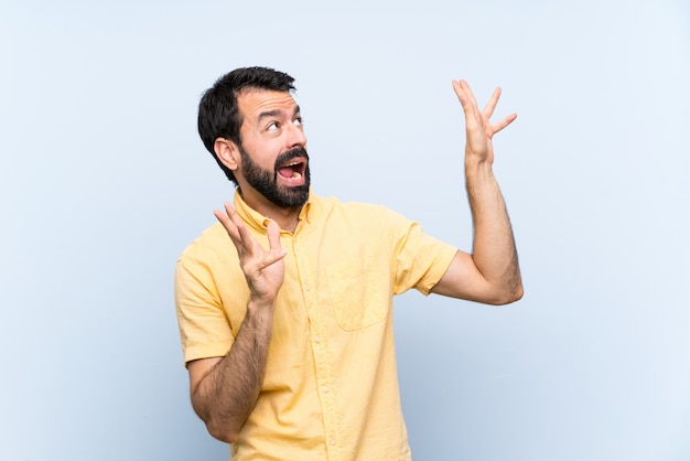 孤立した青い神経と怖がって上のひげを持つ若者 Premium写真
