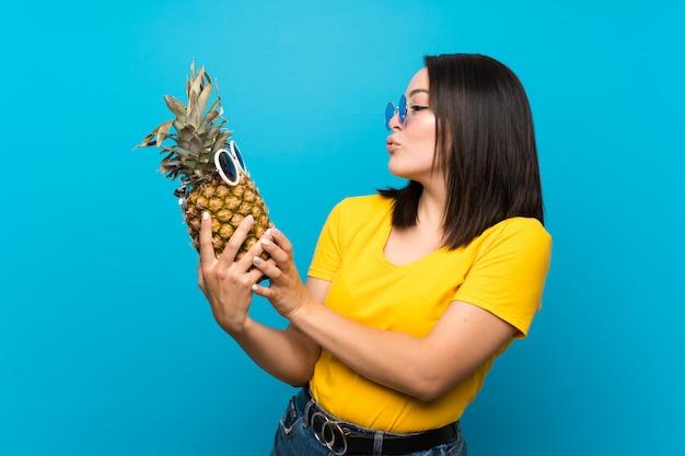 サングラスとパイナップルを保持している分離された青の上のメキシコの若い女性 Premium写真
