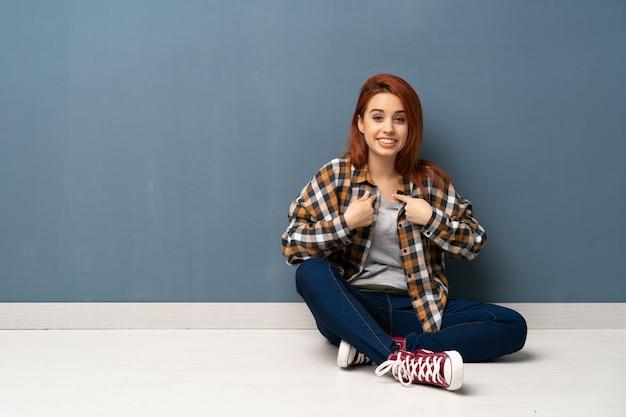 驚きの表情で床に座っている若い赤毛の女性 Premium写真