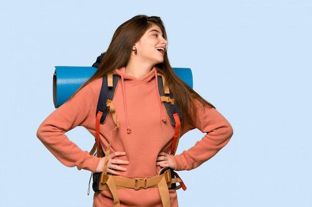ハイカーの女の子が腰に腕でポーズと青に笑って Premium写真