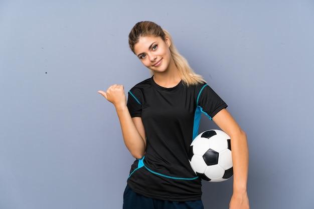 製品を提示する側を指している灰色の壁の上の金髪のフットボール選手ティーンエイジャーの女の子 Premium写真