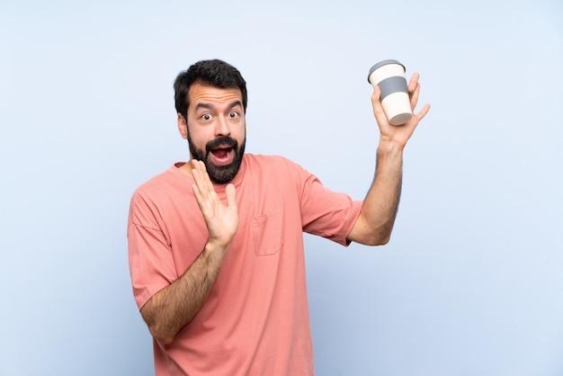 神経質で怖い青のテイクアウェイコーヒーを保持しているひげを持つ若者 Premium写真