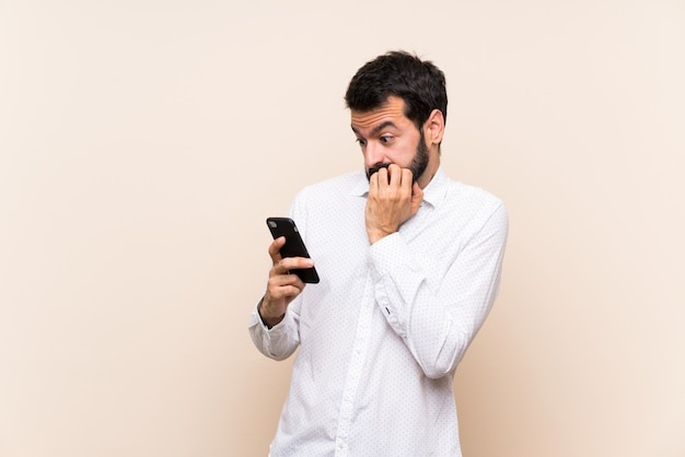 Молодой человек с бородой держит мобильный нервный и страшно положить руки в рот Premium Фотографии