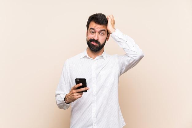 欲求不満の表現と理解していない携帯電話を保持しているひげを持つ若者 Premium写真