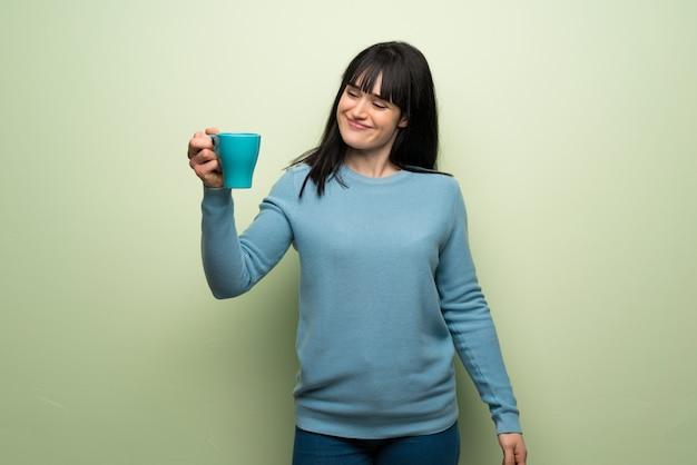 熱い一杯のコーヒーを保持している緑の壁に若い女性 Premium写真