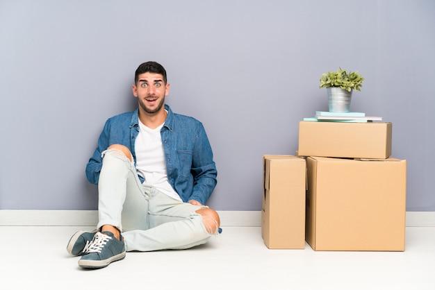 驚きの表情を持つボックスの間で新しい家に移動するハンサムな若い男 Premium写真