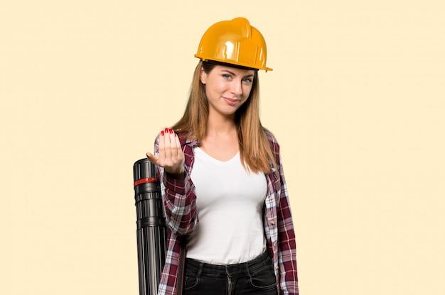 建築家の女性が手に来るように誘います。黄色になったことを嬉しく思います Premium写真