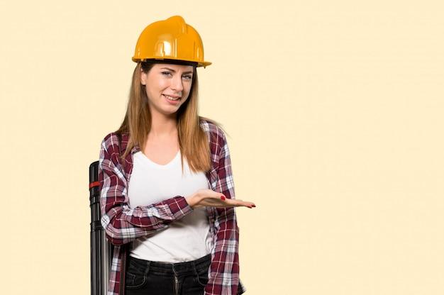 黄色に向かって笑顔を見ながらアイデアを提示する建築家女性 Premium写真