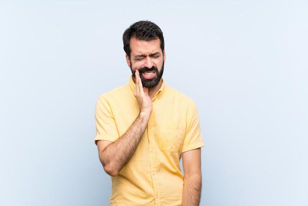 歯痛と分離された青の上のひげを持つ若者 Premium写真