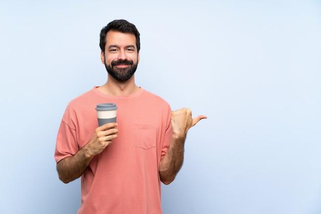 製品を提示する側を指している孤立した青い壁にテイクアウトコーヒーを保持しているひげを持つ若者 Premium写真