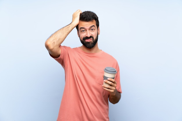 欲求不満の表現と分離された青い壁を越えてコーヒーを保持しているひげと理解していない若い男 Premium写真