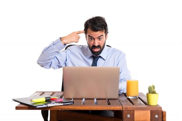 狂ったジェスチャーを作る彼のオフィスのビジネスマン 無料写真