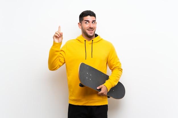指を持ち上げながら解決策を実現しようとしている孤立した白い壁の上のハンサムな若いスケーター男 Premium写真