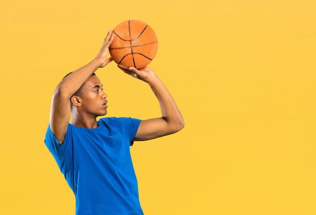 孤立した黄色の壁の上のアフロアメリカンバスケットボールプレーヤー男 Premium写真