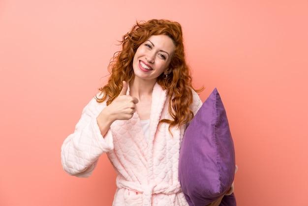 ジェスチャを親指を与えるドレッシングガウンの赤毛の女性 Premium写真