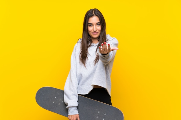 手で来ることを招待して孤立した黄色の壁の上の若いスケーター女性。あなたが来て幸せ Premium写真