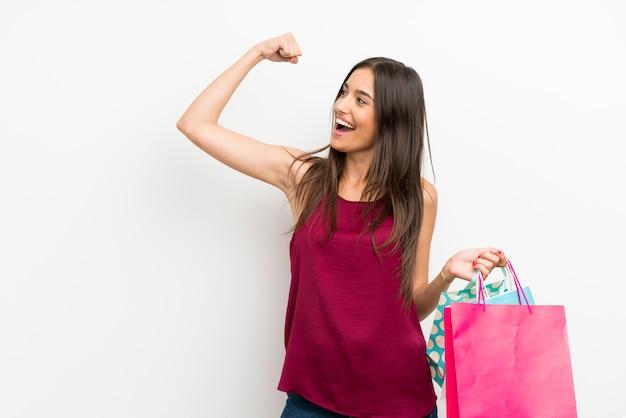 Молодая женщина над изолированной белой стеной держит много сумок Premium Фотографии
