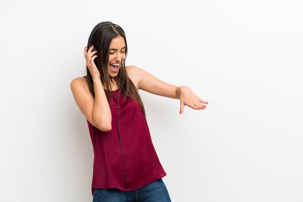ヘッドフォンで音楽を聞いて孤立した白い壁の上の若い女性 Premium写真