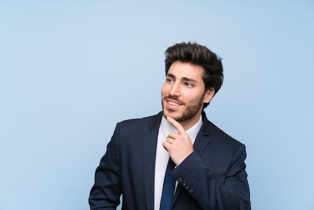見上げながらアイデアを考えて分離の青い壁の上のビジネスマン Premium写真