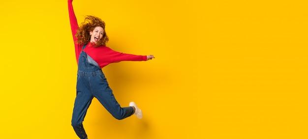 孤立した黄色の壁を飛び越えてオーバーオールで赤毛の女性 Premium写真