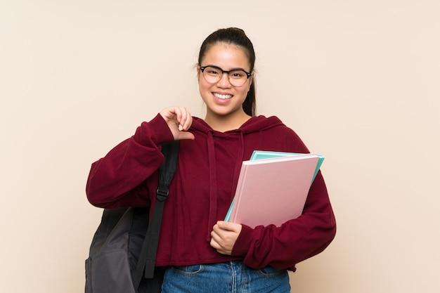 誇りと自己満足の孤立した壁の上の若い学生アジアの女の子女性 Premium写真