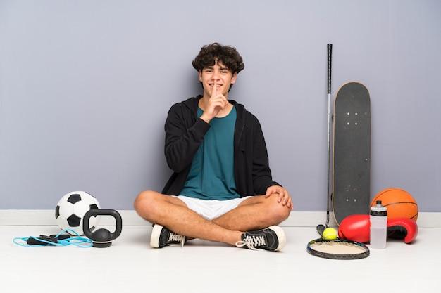沈黙のジェスチャーを行う多くのスポーツ要素の周りの床に座っている若いスポーツ男 Premium写真