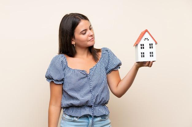小さな家を保持している孤立した壁の上の少女 Premium写真