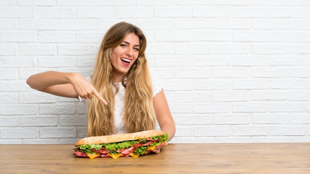 Счастливая молодая белокурая женщина держа большой сандвич Premium Фотографии
