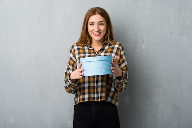 贈り物を与えられたので驚いたグランジ壁の上の若い赤毛の女の子 Premium写真
