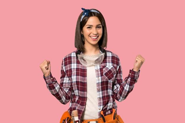 孤立したピンクの壁に勝利を祝っている若年労働者の女性 Premium写真