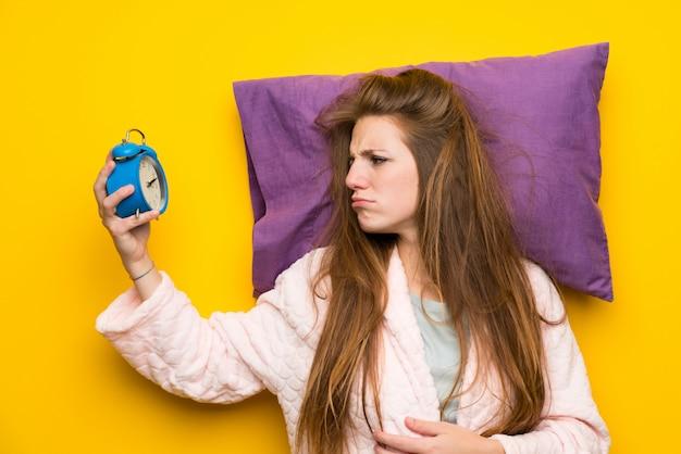 ビンテージ時計を保持しているベッドでドレッシングガウンの若い女性を強調しました。 Premium写真